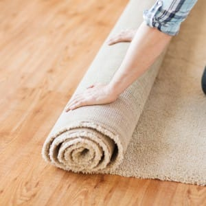 Man laying carpet on a wooden floor